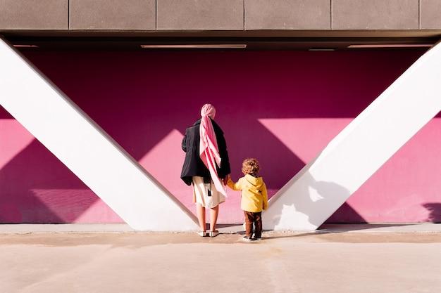 Больная раком женщина, пожимая руку своему трехлетнему сыну в платке, глядя на розовую стену. концепция борьбы с раком
