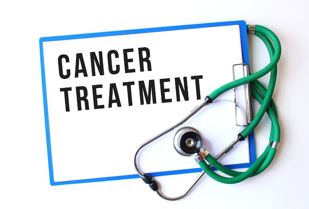 Cancer treatment text on medical folder with documents and stethoscope on white background. medical concept.
