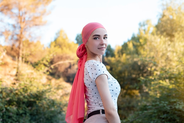 Cancer woman with a pink headscarf on a beautiful day