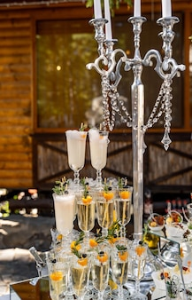 Candelstick and three vertical lines of crystal champagne glasses. rich and fashionable decoration. closeup.
