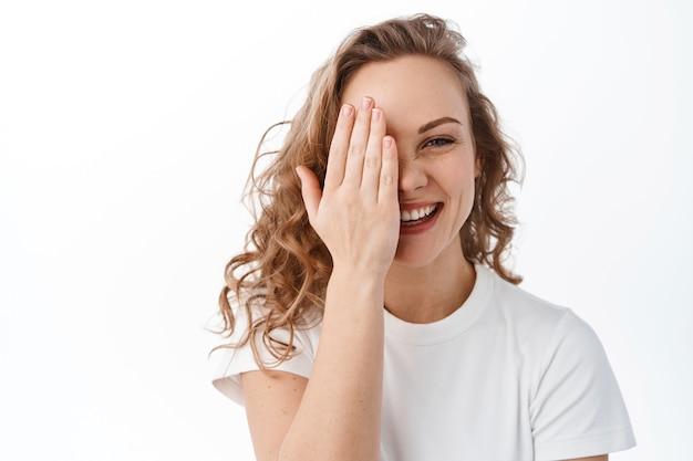 率直な魅力的な女性は手と笑顔の後ろに顔の半分を隠し、笑って自然な幸せな表情を見せ、白い壁の上に立っています