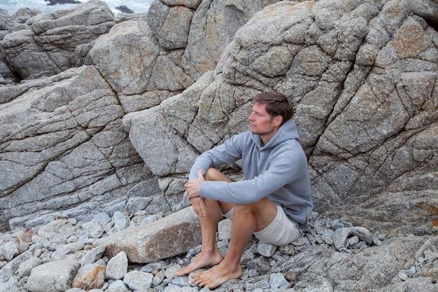 岩の多い海岸に座っている率直な本物のミレニアル世代の男が日の出を迎えます