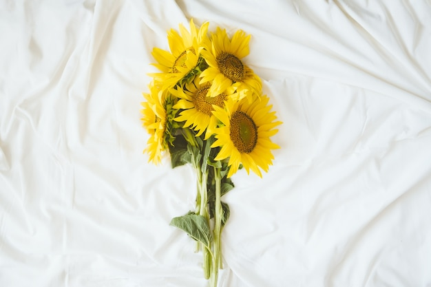 Candid authentic yellow sunflowers bouquet on fabric white background. background with bouquet of yellow sunflowers on white bed sheet. sunny days, summer floral concept.