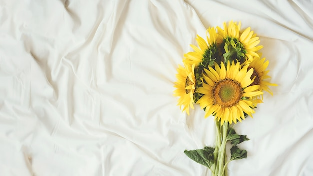 Candid authentic yellow sunflowers bouquet on fabric white background background with bouquet of