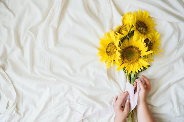 패브릭 흰색 배경에 솔직한 정통 노란 해바라기 꽃다발. 하얀 침대 시트에 노란 해바라기 꽃다발이 있는 배경. 화창한 날, 여름 꽃 개념입니다.