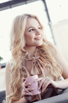 Candid beautiful blonde woman with tea or coffee cup