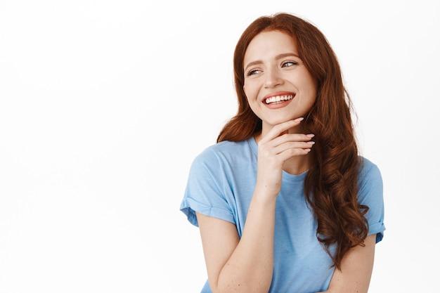 솔직한 생강 소녀는 웃고, 하얀 치아를 웃고, 행복하고 편안한 자연스러운 표정으로 왼쪽 카피스페이스를 옆으로 바라보며 흰색 위에 서 있습니다.
