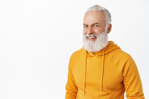 Откровенный счастливый старик с длинной стильной бородой, смеющийся и улыбающийся, выглядит счастливым, в современной оранжевой толстовке с капюшоном, стоит над белой стеной