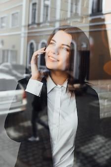 カフェで電話で話している実業家の率直な画像。幸せな晴れた日!