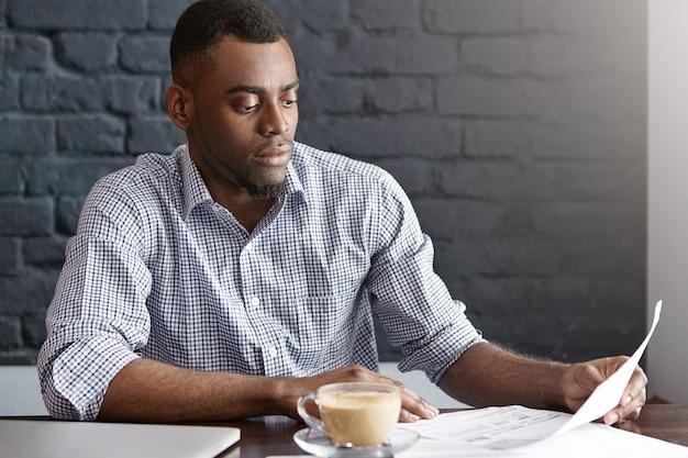 ドキュメントを保持している市松模様のシャツで魅力的な浅黒い肌の実業家の率直な屋内撮影