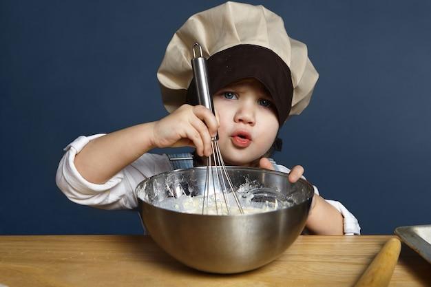Candido ritratto isolato di una seria ragazzina di 5 anni in un grande cappello da cuoco che sbatte farina, uova e latte nella ciotola mentre prepara i pancake da sola. ricetta, cucina, cottura al forno, cucina e concetto di infanzia