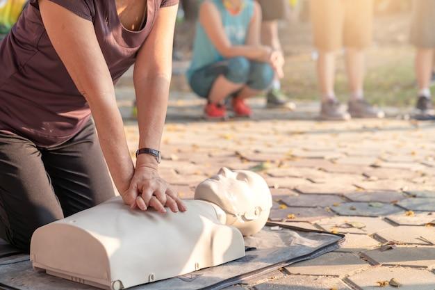 Кандидат в зрелую азиатскую женщину или более старшую женщину бегуна тренирующуюся на cpr, демонстрирующую класс в наружном парке и кладущий руки на куклу cpr на груди. обучение оказанию первой помощи людям с сердечными приступами или спасателям.