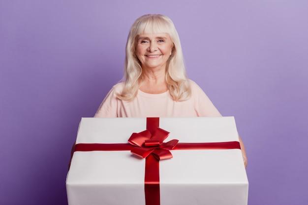 Откровенная старуха держит большую подарочную коробку, изолированную на фиолетовом фоне