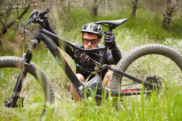 壊れた電動自転車の前の草の上に座っている防護服を着た集中力のある若いライダーの率直な屋外撮影。何が問題なのかを理解しようとしています。自転車の前に電子バイクをチェックする男