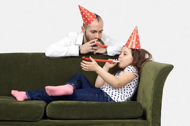 Candido ritratto di adorabile bambina graziosa che gode della festa di compleanno a casa, sdraiato sul divano e soffiando il corno della festa insieme al suo giovane padre con la barba lunga