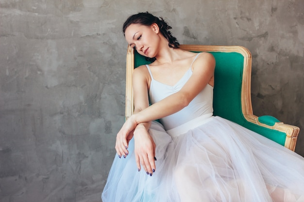 Candid portrait of ballet dancer ballerina in beautiful light blue dress tutu skirt posing sitting on vinage chair in loft studio