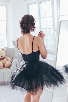 Candid portrait of ballet dancer ballerina in black dress in front of mirror