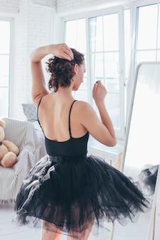 Candid portrait of ballet dancer ballerina in black dress in front of mirror