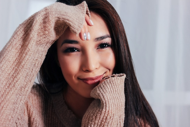 Candid portrait of sensual smiling asian girl young woman with dark long hair in cozy beige sweater