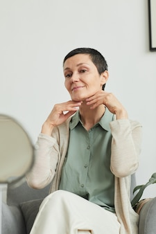 Candid portrait of smiling mature woman looking beautiful while doing makeup at home