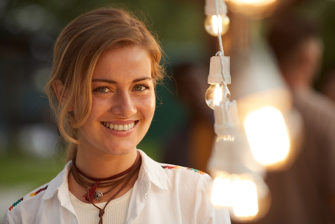 Candid portrait of smiling woman standing by lights at outdoor party