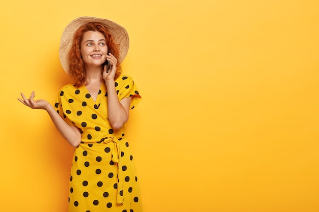Candid redhead woman posing in yellow polka dress and straw hat