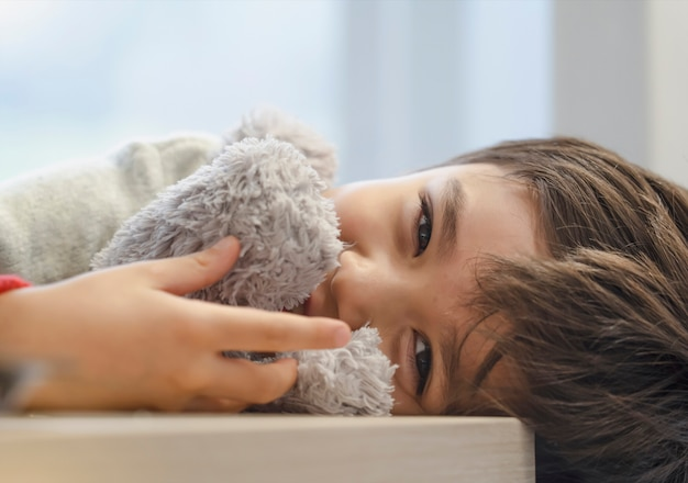 Candid shot adorable kid lying on table looking at camera with smiling face, child boy relaxing at home playing with soft toy, positive children concept