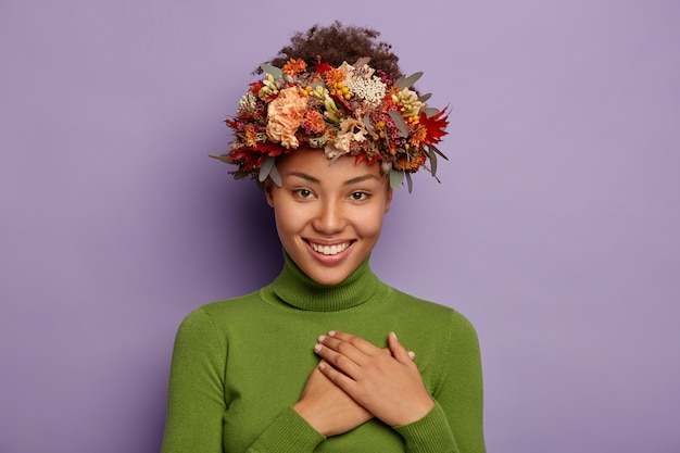 Candid shot of attractive smiling woman feels thankful, ouches chest gratefully, wears autumn wreath, poses indoor in casual wear