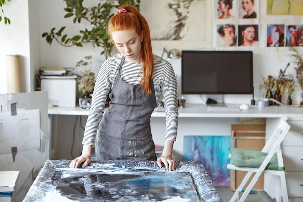 Candid shot of attractive thoughtful ginger girl artist standing at desk while working on painting, thinking over what to add to make it look perfect. people, hobby, creativity and art concept