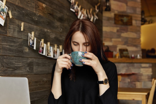 Candid shot of beautiful brunette woman freelancer in black clothing drinking coffee or tea out of large cup during small break while working remotely at cafe, sitting in front of open laptop computer