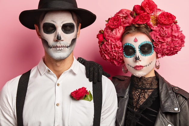 Candid shot of calm woman and man zombie with eyes closed, have artistic makeup, traditional holiday costumes, celebrate day of dead, have scary look, isolated over pink background.