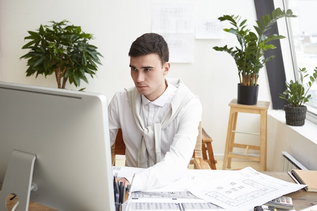 Candid shot of concentrated young brunette man engineer dressed formally working on generic computer, having serious look, sitting in his modern office, surrounded with papers and blueprints