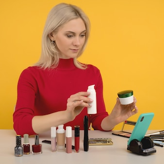 Candid shot of cute young caucasian woman blogger presenting beauty products and broadcasting live video to social network, talks about foundation cream while recording everyday make up tutorial