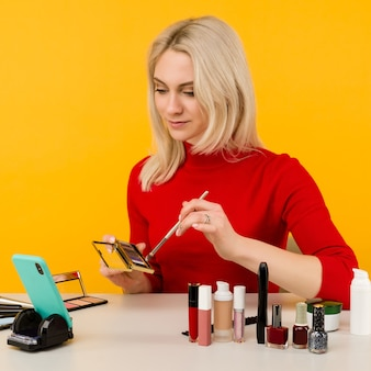 Candid shot of cute young caucasian woman blogger presenting beauty products and broadcasting live video to social network, using brush to apply eyeshadow while recording everyday make up tutorial
