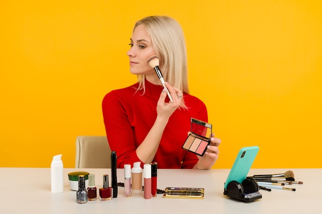 Candid shot of cute young caucasian woman blogger presenting beauty products and broadcasting live video