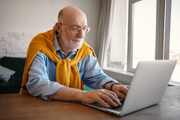 Candid shot of fashionable elegant mature sixty year old man with gray beard and bald head having focused look, using wifi generic laptop, touch typing fast. people, age and gadgets concept