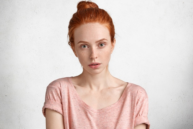 Candid shot of freckled adorable woman with serious expression, looks directly into camera, dressed in casual t shirt, isolated over white concrete