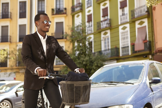 Candid shot of happy ecologically conscious successful afro american office worker wearing sunglasses and formal suit commuting to work on bicycle, standing with two-wheeled vehicle in urban setting
