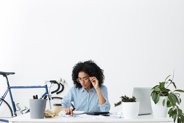 Candid shot of hardworking businesswoman with curly hair focused on paperwork