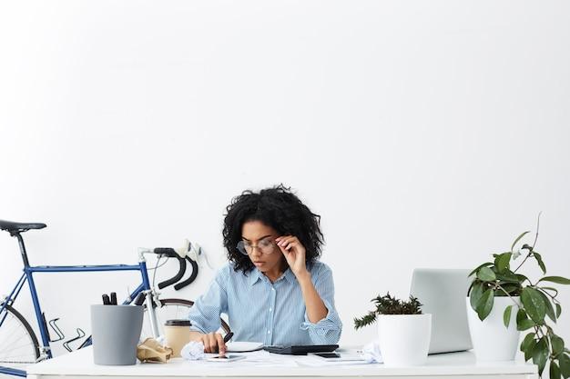 Candid colpo di imprenditrice laboriosa con i capelli ricci concentrati sul lavoro di ufficio