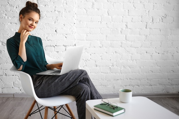 Candid shot of joyful beautiful young caucasian female freelancer using generic laptop for distant work, sitting casually in chair at coffee table with mug, book and eyeglasses. people and technology