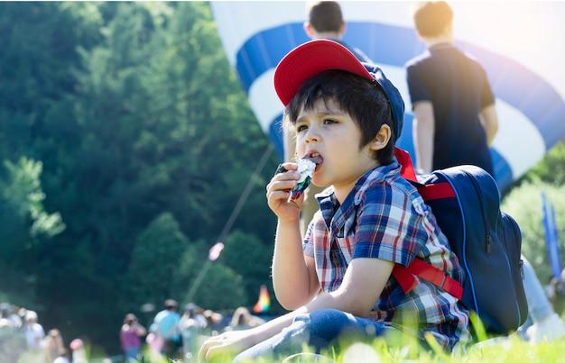 率直なショットキッドぼやけている人々の背景を持つチョコレートを食べる芝生のフィールドに座っている子供、熱気球が解放される準備ができるのを待っている間、空腹の子供男の子は甘いものを食べます。夏の野外活動