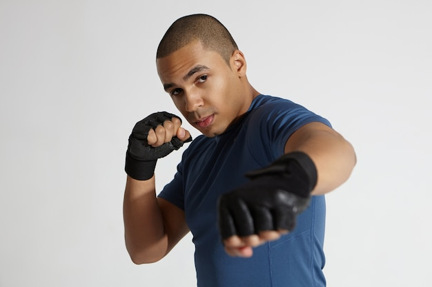 Candid shot of muscular serious young dark skinned male boxer wearing boxing bandage and training outfit practicing martial arts indoors. strong handsome african bodybuilder working out in gym