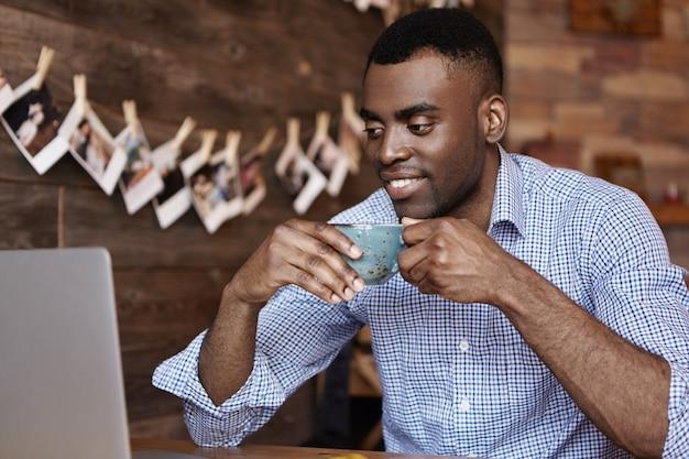 マグカップを保持している正式なシャツの魅力的な若いアフリカ系アメリカ人男性の率直なショット