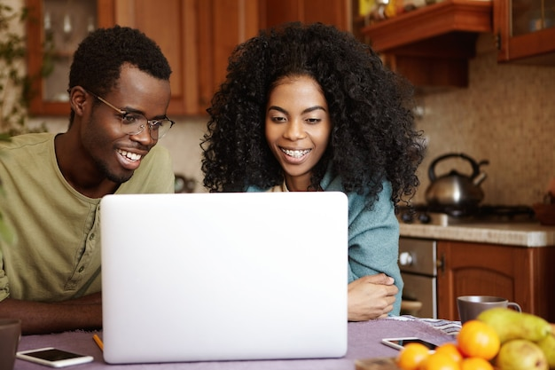 Откровенный снимок красивой молодой афро-американской пары, сидящей за кухонным столом перед открытым ноутбуком