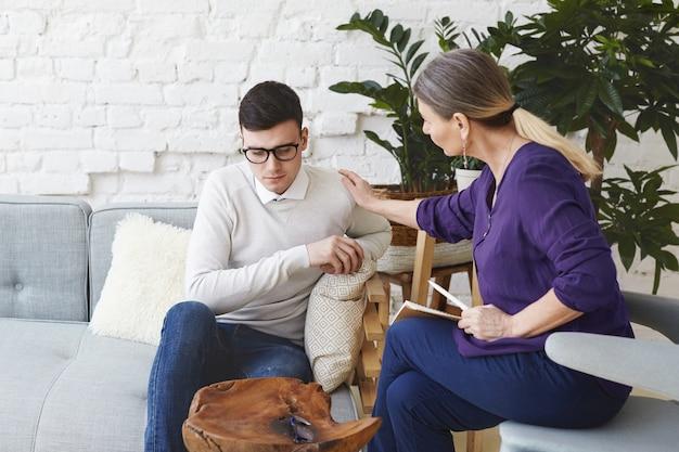 상담 세션을 갖는 동안 어깨로 그녀의 젊은 남성 환자를 만지고 동정과 지원을 표현하는 그녀의 50 대 캐주얼 옷을 입은 전문 여성 심리 치료사의 솔직한 샷