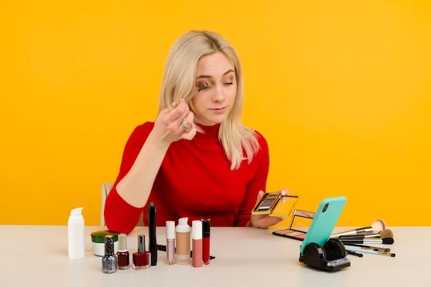 Откровенный снимок симпатичной молодой кавказской женщины-блогера, представляющей косметические товары и транслирующей прямое видео в социальной сети, используя кисть для нанесения теней для век во время записи урока по ежедневному макияжу
