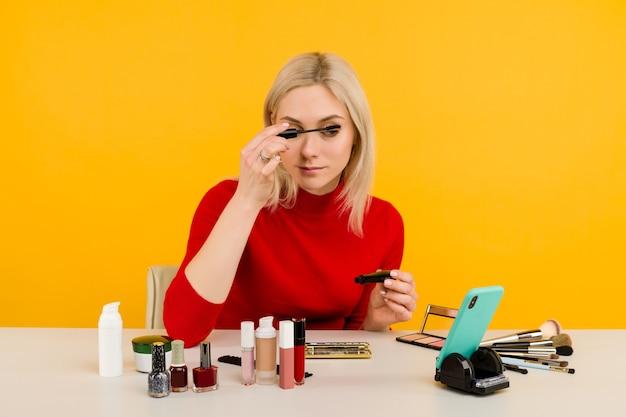 Откровенный снимок симпатичной молодой кавказской женщины-блогера, которая представляет косметические товары и транслирует видео в прямом эфире в социальной сети, используя кисть для нанесения туши во время записи урока по макияжу.