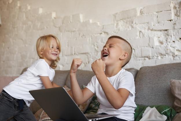 Откровенный снимок эмоционального экстаза подростка с подтяжками, сидящего на диване со своим младшим братом, использующего портативный компьютер, кричащего и размахивающего кулаками, радующегося своей победе в видеоигре