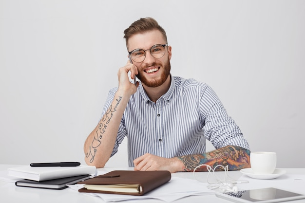 ファッショナブルな刺青の男の率直なショットは、ロールアップした袖と丸いメガネのシャツを着ています